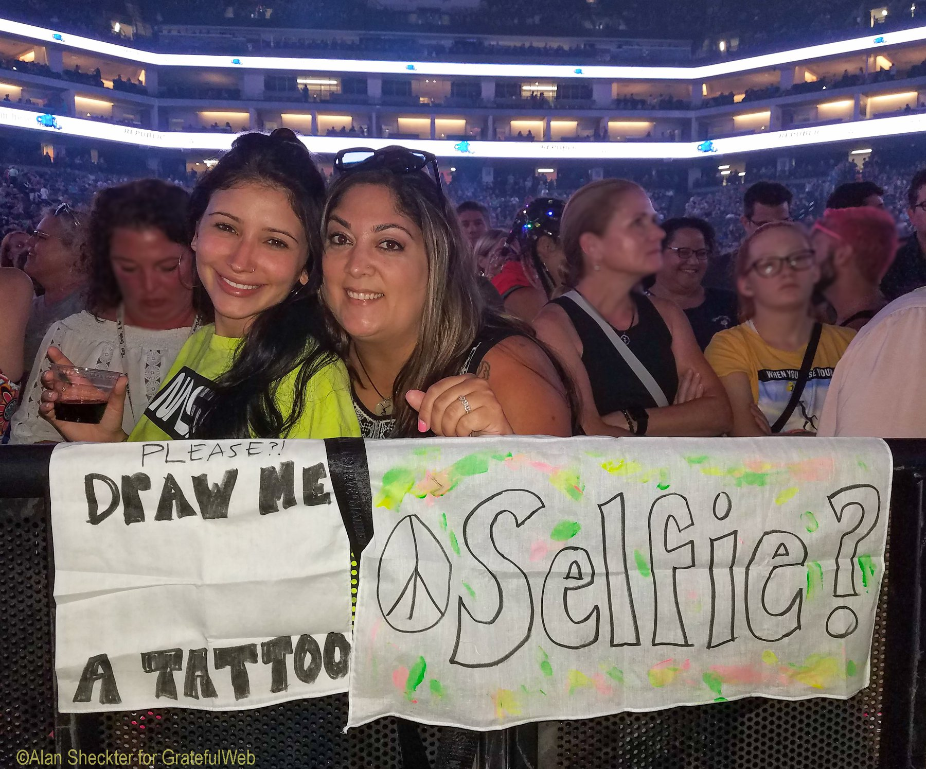 Perched in front of the stage, Emily Rivera (right) and her friend Dee, tried to entice Dave Matthews, who is also a visual artist, to come down and hang